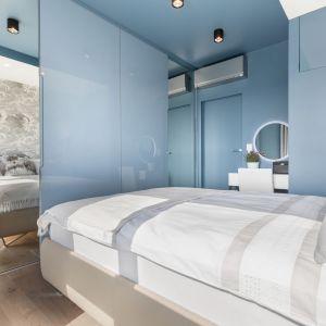 Aby optycznie powiększyć sypialnię we fronty szafy wkomponowane zostały lustra. Projekt i zdjęcia: Monika Staniec