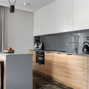Mała, otwarta kuchnia w bieli, szarości i naturalnym drewnie. Projekt: pracownia M-Studio. Fot. Radek Słowik