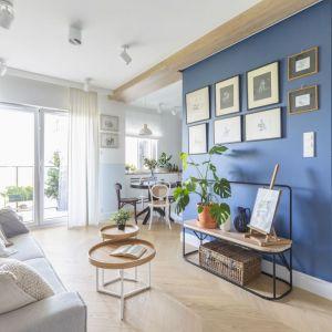 Aranżacja małego salonu. Na podłodze jodełka drewniana w chłodnym kolorze. Na ścianie niebieska farba i galeria grafik. Projekt: Joanna Dziurkiewicz, Tworzywo studio. Zdjęcia Pion Poziom
