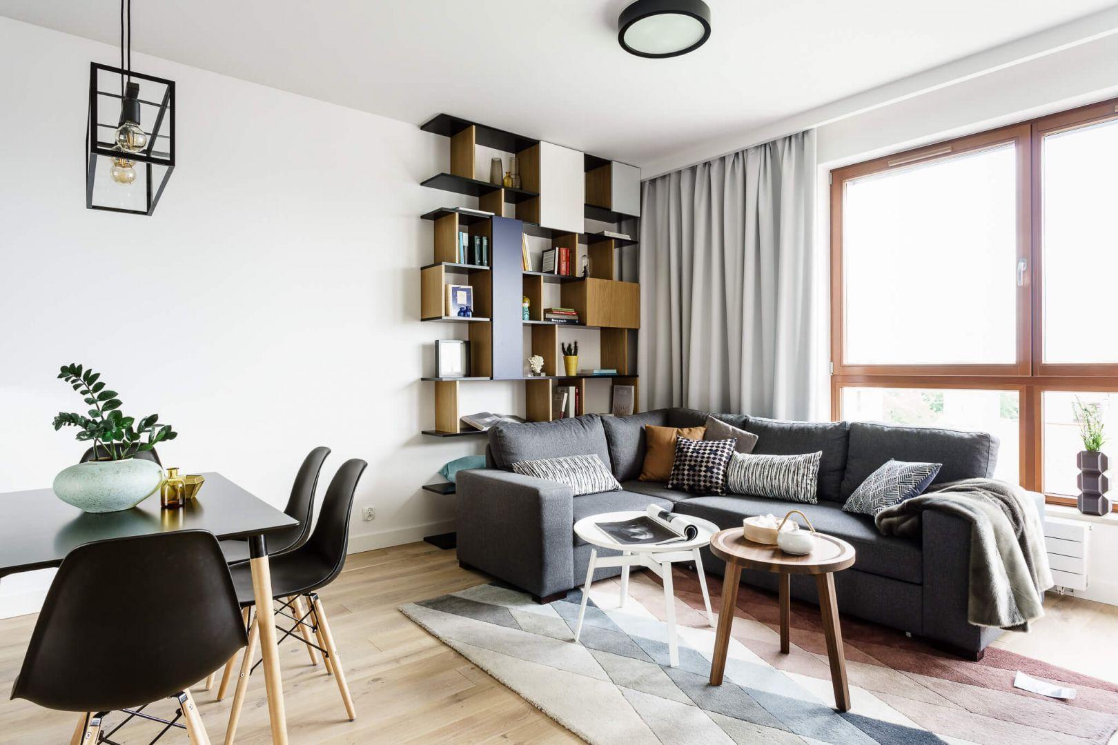 Aranżacja małego salonu. Na podłodze wzór prostej drewnianej deski. Na ścianie jasna farba i ciekawe półki. Projekt: Magdalena Bielicka, Maria Zrzelska-Pawlak, pracownia Magma. Fot. Fotomohito