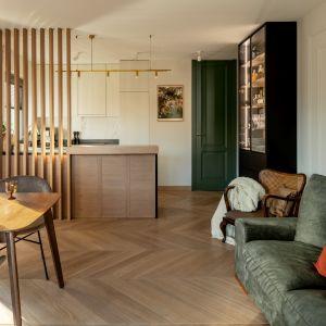 Nowoczesna kuchnia otwarta na salon, oddzielona ażurową ścianką z drewnianych lameli. Projekt: Finchstudio. Stylizacja i fot. Aleksandra Dermont