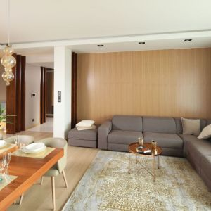 Aranżacja salonu jest nowoczesna i elegancka. Ściany wykończone drewnianymi panelami świetnie pasuje o kanapy oraz złotych akcentów. Projekt: Laura Sulzik. Fot. Bartosz Jarosz