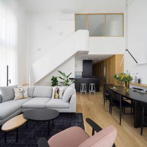 Salon z antresolą w mieszkaniu w bloku. Pastelowe kolory połączono tu z matową czernią i ciepłym drewnem. Projekt: 3XEL. Fot. Dariusz Jarząbek