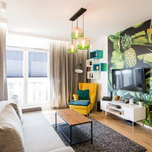 Mały jasny salon  w bloku - przytulności dodają dekoracje i piękny fotel w musztardowym kolorze. Projekt: The Space Fot. Piotr Czaja