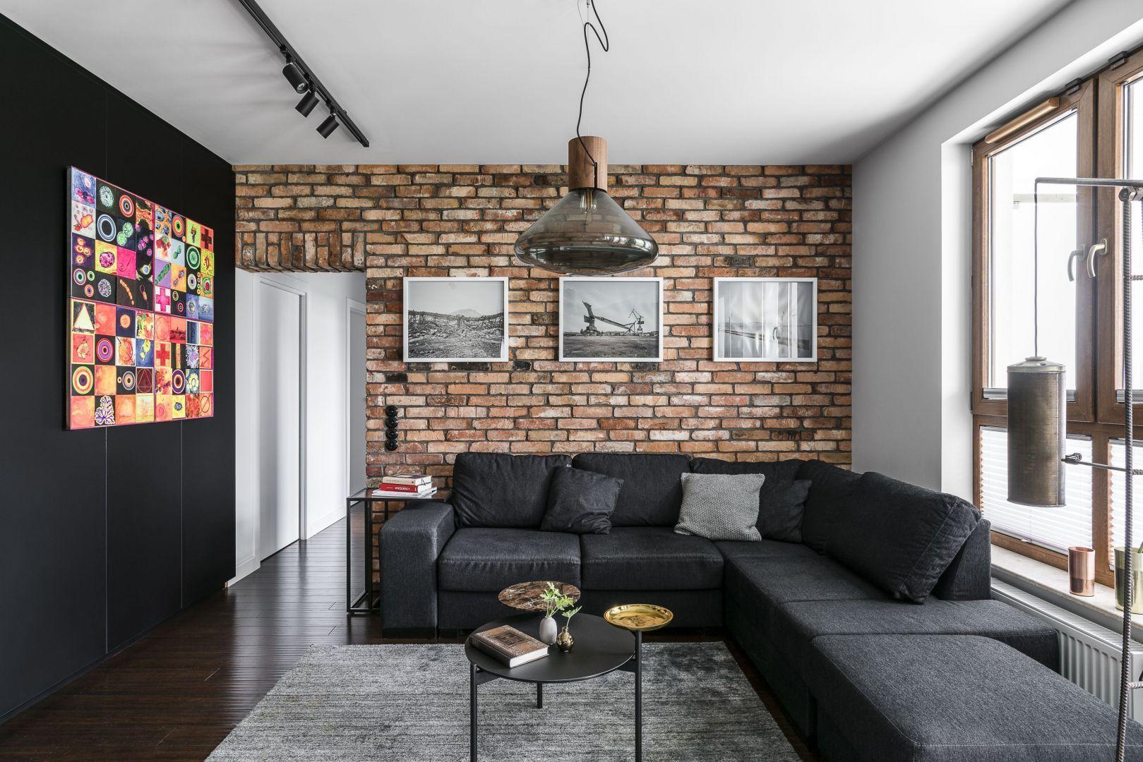 Cegła pięknie zdobi ścianę za kanapą w nowoczesnym salonie. Świetnie pasuje do eleganckie czerni i ciemnych szarości. Projekt: pracowania Magma. Fot. Fotomohito