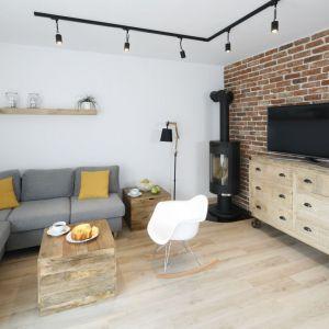 Ścianę za telewizorem wykończono cegłą, które pięknie pasuje do bieli, szarości oraz drewna zastosowanego w salonie. Projekt: Katarzyna Uszok. Fot. Bartosz Jarosz