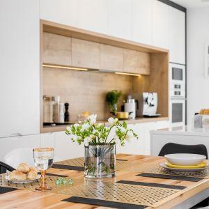 Salon od kuchni oddziela duża wyspa z szufladami i kamiennym blatem. Projekt: Joanna Nawrocka, JN Studio Joanna Nawrocka. Fot. Łukasz Bera