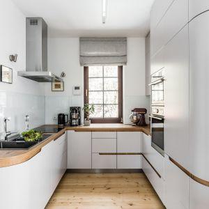 Nowoczesna biała kuchnia z drewnianym blatem i drewnianą podłogą. Projekt: Magdalena Bielicka, Maria Zrzelska-Pawlak, Pracownia Magma. Fot. Fotomohito