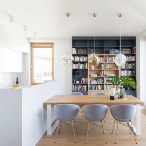 Biała kuchnia i jadalnia z drewnianym stołem i drewnianą podłogą. Projekt: Renee's Interior Design Fot. Marta Behling Pion Poziom - Fotografia Wnętrz