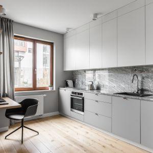 Biało-szara kuchnia z drewnianą podłogą. Autorzy projektu: Raca Architekci. Zdjęcia:  Fotomohito