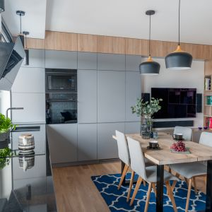 Szara zabudowa do samego sufitu sprawia, że nie widzimy, gdzie kończy się kuchnia, a gdzie zaczyna salon. Projekt: Ewelina Para, RED design. Fot. Adam Woropiński www.bardzo.photo.pl