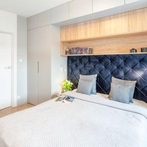Dekoracyjny, granatowy zagłówek pięknie prezentuje się w sypialni. To aranżacyjna wisienka na torcie w tym pomieszczeniu. Projekt: Ewelina Para, RED design. Fot. Adam Woropiński www.bardzo.photo.pl