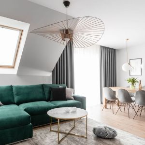Zielona kanapa w białym salonie. Projekt: Estera i Robert Sosnowscy, Studio Projekt. Fot. Fotomohito