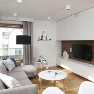 Salon urządzony został w załamanych odcieniach bieli, które nadają mu przytulny klimat. Projekt Przemysław Kuśmierek. Fot. Bartosz Jarosz