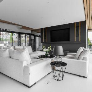 W białym salonie piękne zastosowano elegancką czerń i przytulne drewno. Projekt: Joanna Ochota, Archimental Concept JOana. Fot. Mateusz Kowalik