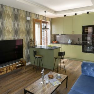 Drewniana szafka z dekoracyjnymi frontami w salonie. Projekt: Magdalena Miśkiewicz. Fot. Łukasz Zandecki