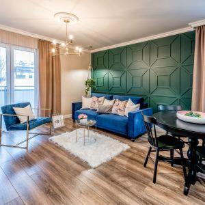 Ściana w salonie ze sztukaterią, pomalowana na zielony kolor w butelkowym odcieniu. Projekt: Marta Piórkowska-Paluch. Zdjęcia: Andrzej Czechowicz, Foto Studio Wrzosy