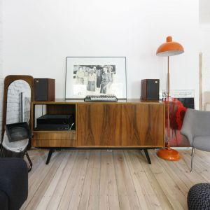 Drewniana komoda pięknie wygląda na tle jasnej ściany w salonie. Projekt: Ewelina Pik. Fot. Bartosz Jarosz