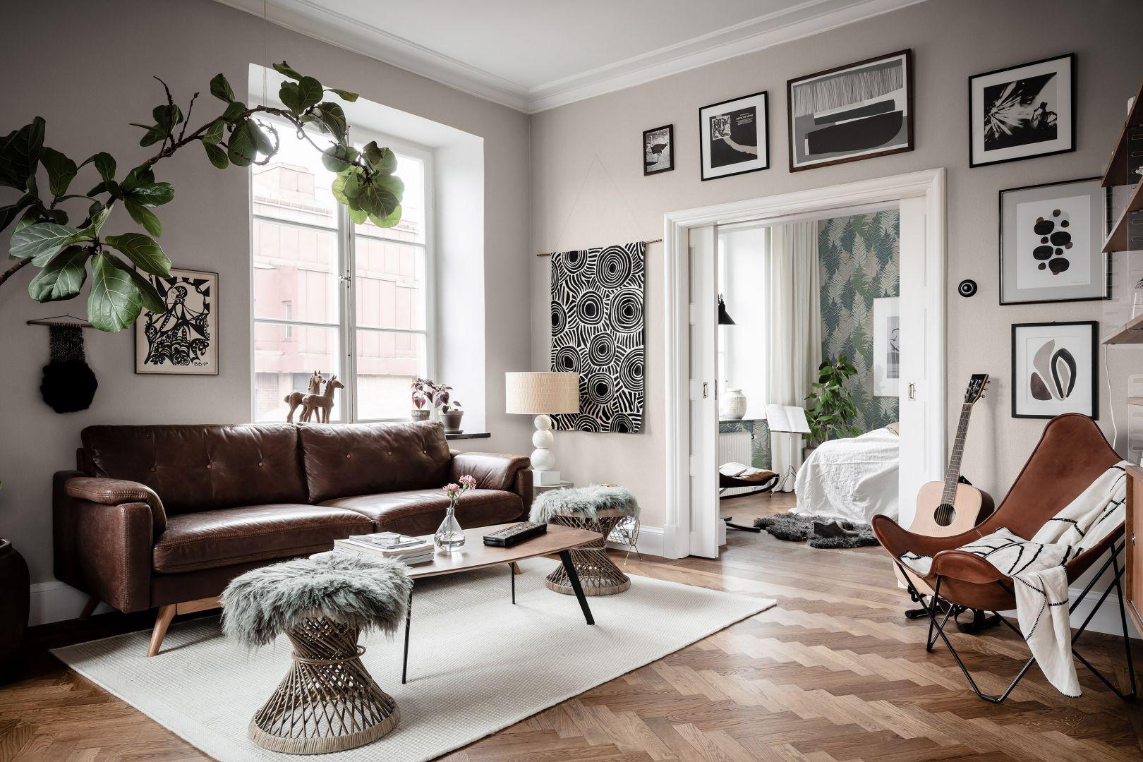 Salon w skandynawskim stylu ze ścianami udekorowanymi czarno-białymi grafikami i jasną tapetą Boras Tapeter. Sprzedaż: Impresje.pl