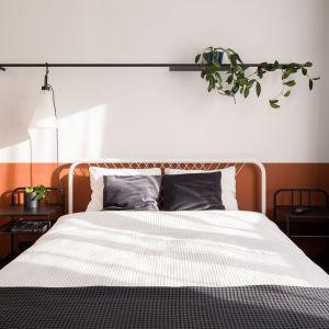 W centrum znajduje się łóżko z metalową ramą, a po lewej  – blat roboczy do pracy w domu. Projekt: pracownia 3XEL. Fot. Dariusz Jarząbek