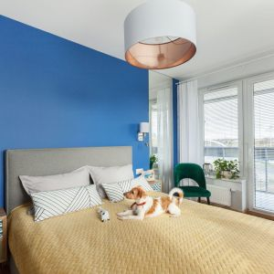 Ściana w kolorze kobaltu stała się tłem dla prostego, tapicerowanego łóżka w sypialni. Projekt: Justyna Mojżyk, poliFORMA. Fot. Monika Filipiuk-Obałek