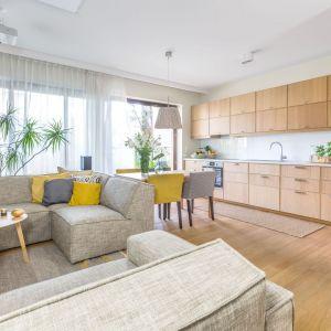 Salon połączony z kuchnią pięknie ożywiają żółte dodatki wnoszące do wnętrza wiosenny klimat. Projekt: Dorota Kudła. Fot. Pion Poziom