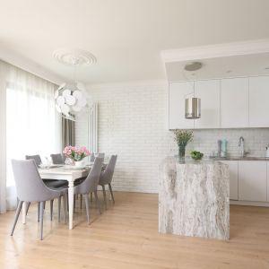 Ściana nad blatem w kuchni wykończona jest białą cegłą. Projekt: Laura Sulzik. Fot. Bartosz Jarosz