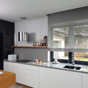 Ściana nad blatem w kuchni wykończona jest szkłem w szarym kolorze. Projekt: Laura Sulzik. Fot. Bartosz Jarosz