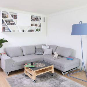Niebieska lampa stojąca w jasnym, nowoczesnym salonie. Projekt: Laura Sulizik. Fot. Bartosz Jaosz