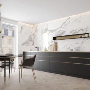 Modny pomysł na ścianę nad blatem w kuchni. Utrzymana w bieli kolekcja płytek Calacatta White oddaje sieć żyłek białego marmuru statuario. Producent Cerrad.
