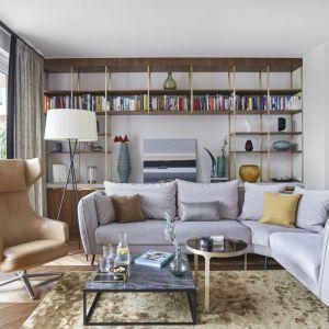 Ścianę za kanapą w salonie wykorzystano bardzo praktycznie. Mamy tu sporo półek, a więc i sporo miejsca na przechowywanie. Projekt: Joanna Kiryłowicz. Fot. Celestyna Król
