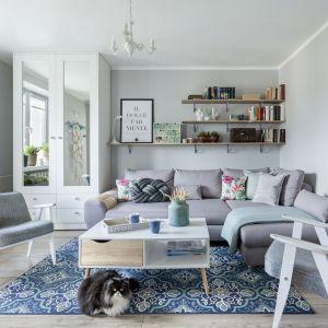Trzy, wiszące półki na ścianie za kanapą są piękną ozdob ą salonu. Projekt Justyna Mojżyk. Fot. Monika Filipiuk-Obałek