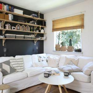 Wiszące, drewniane półki to świetny pomysł na dekorację ściany za kanapą w salonie. Projekt: Justyna Majewska. Fot. Bartosz Jarosz