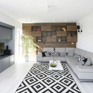 Drewniane półki na ścianie za kanapą w salonie zestawiono z jasną podłogą w chłodnym odcieniu. Projekt: Ewelina Pik, Maria Biegańska. Fot. Bartosz Jarosz