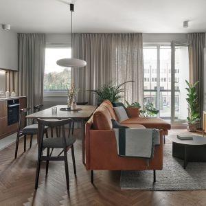 Salon od części kuchenno-jadalnianej oddziela sofa. Projekt Raca Architekci . Fot. Tom Kurek