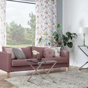 Pudrowy róż i modne kwiatowe wzory na zasłonach w salonie. Fot. Dekoria
