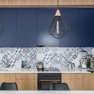 Ścianę nad blatem zdobią kafle z majolikami w różnych odcieniach koloru niebieskiego. Projekt Magma. Fot. Fotomohito