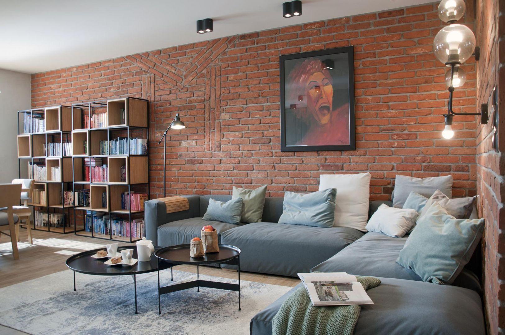 Ściana za kanapą w salonie wykończona jest czerwoną cegłą pochodząca z rozbiórki. Projekt: Ewelina Mikulska-Ignaczak, Mikulska Studio. Fot. Jakub Ignaczak, K1M1