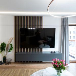 Ściana z telewizorem wykończona została drewnianymi lamelami. Autorka projektu: Malwina Kuzera. Fot. Piotr Seweryn, SewiMedia
