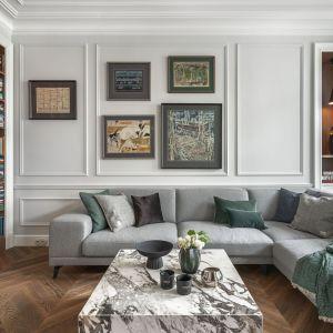 Ściana za kanapą w salonie wykończona jest sztukaterią w szarym kolorze. Projekt: Whitecastle. Fot. Tom Kurek