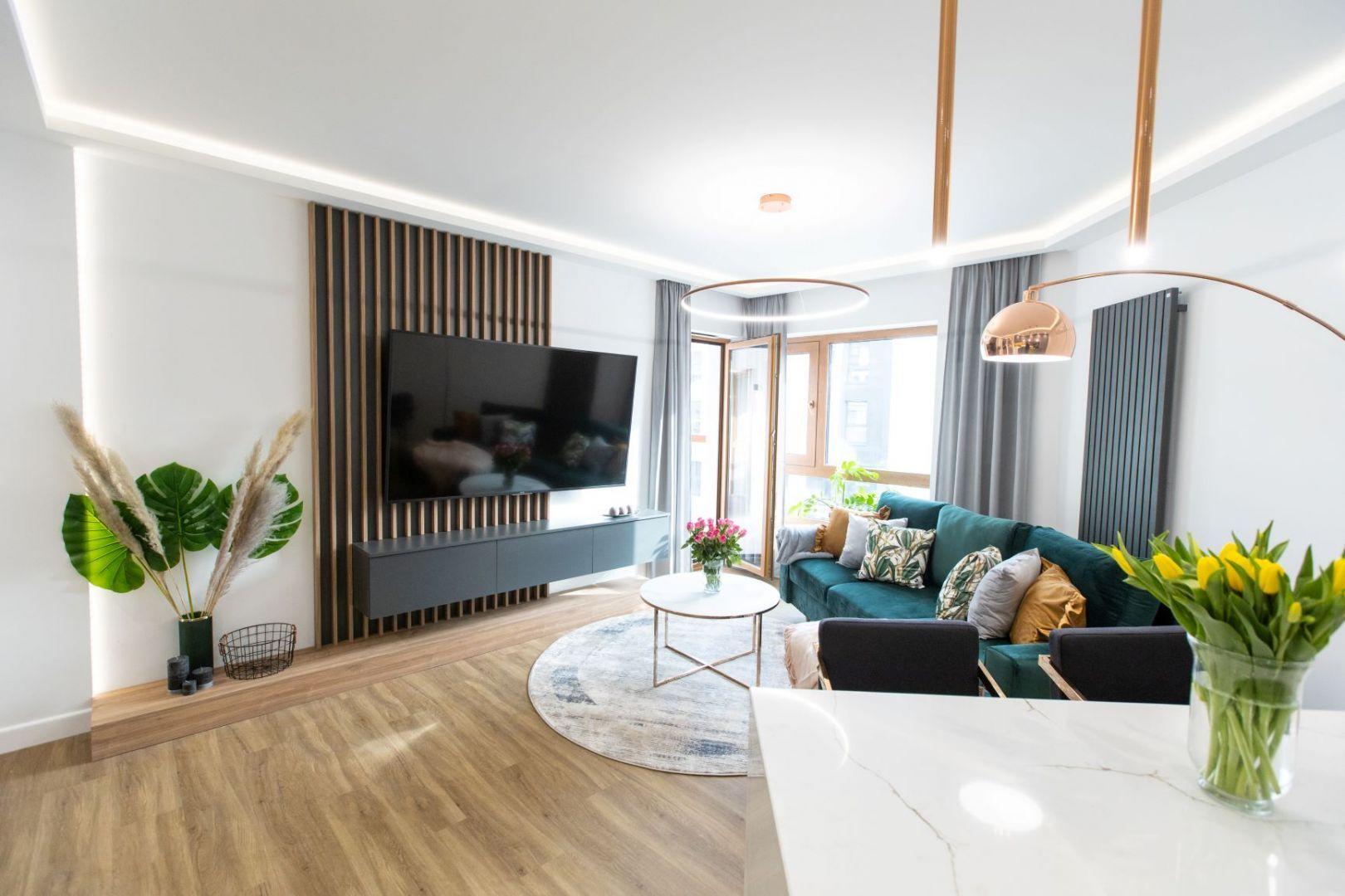 Jak urządzić salon w bloku? Pomysł na aranżację z zieloną sofą i drewnianymi lamelami na ścianie z telewizorem. Projekt: Malwina Kuzera. Fot. Piotr Seweryn, SewiMedia