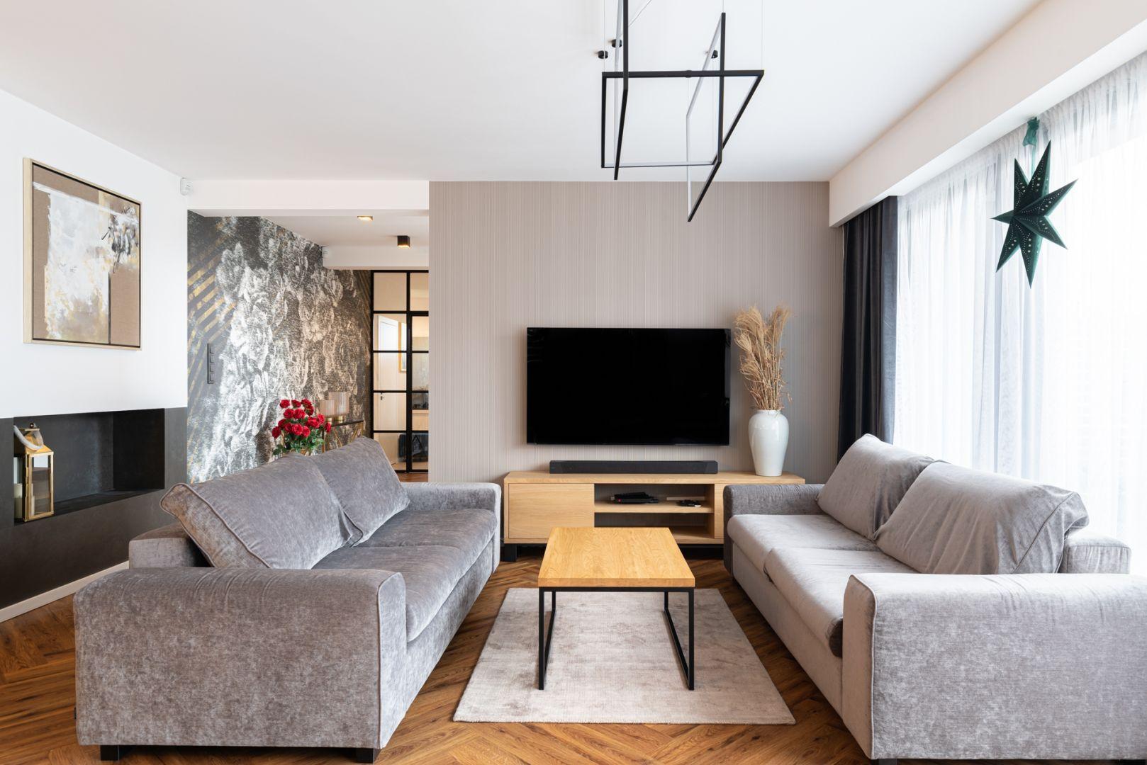 Ściana za telewizorem wykończona jest jasną, subtelną tapetą. Projekt: Aleksandra Michalak x Dekorian Home. Fot. Łukasz Michalak