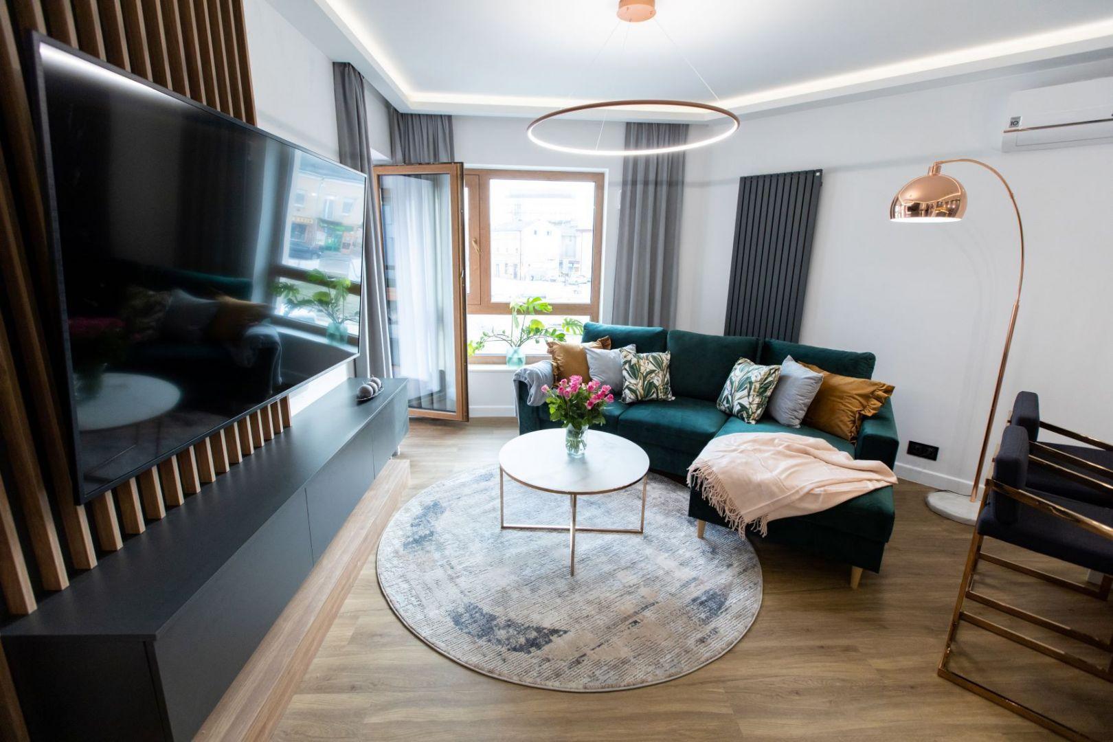 W tym salonie projektantka postawiła na szare zasłony i dywan oraz poduszki w kolorach natury oraz kontrastowe musztardowe. Autorka projektu: Malwina Kuzera. Fot. Piotr Seweryn, SewiMedia