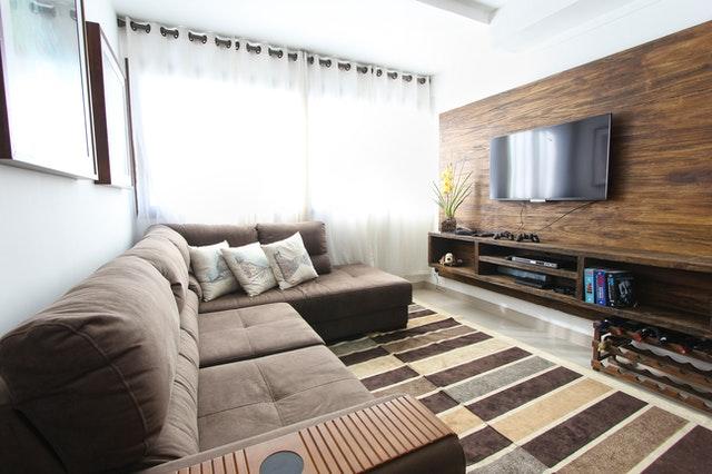 Biel i brąz oraz proste w formie meble doskonale podkreślają nowoczesny wystrój małego salonu w bloku.