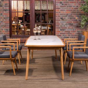 Ergonomiczne krzesła zapewnią komfort i wygodę podczas wspólnych posiłków w gronie najbliższych. Miękkie poduchy, podobnie jak w przypadku mebli wypoczynkowych, dbają o wygodę. Kolekcja Bouhus. Fot. Kler