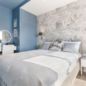 Głównym elementem w nowoczesnej sypialni jest kultowa tapeta na ścianie za łóżkiem. Projekt i zdjęcia: Monika Staniec