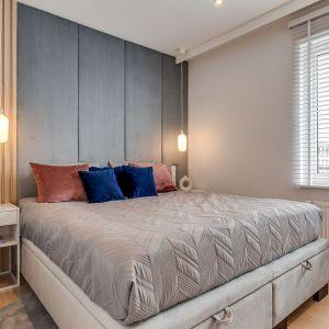 Tapicerowany zagłówek i drewniane panele zdobią ścianę w nowoczesnej sypialni. Projekt: Pracownia Architektury Wnętrz FOORMA. Fot. Radosław Sobik