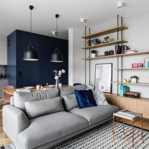Półki łączące metal i drewno pięknie prezentują się w salonie urządzonym w skandynawskim stylu. Projekt: Raca Architekci. Zdjęcia: foto&mohito