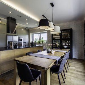 Modna kuchnia z dużą wyspą oraz stołem jadalnianym. Projekt: Dominika Jurczak, DK architektura wnętrz. Fot. Krzysztof Czapor