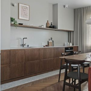 Ściana nad blatem w kuchni wykończona została szarym konglomeratem kwarcowym marki Silestone od Cosentino. Ten sam materiał został zastosowany na blacie. Projekt: Raca Architekci. Fot. Tom Kurek
